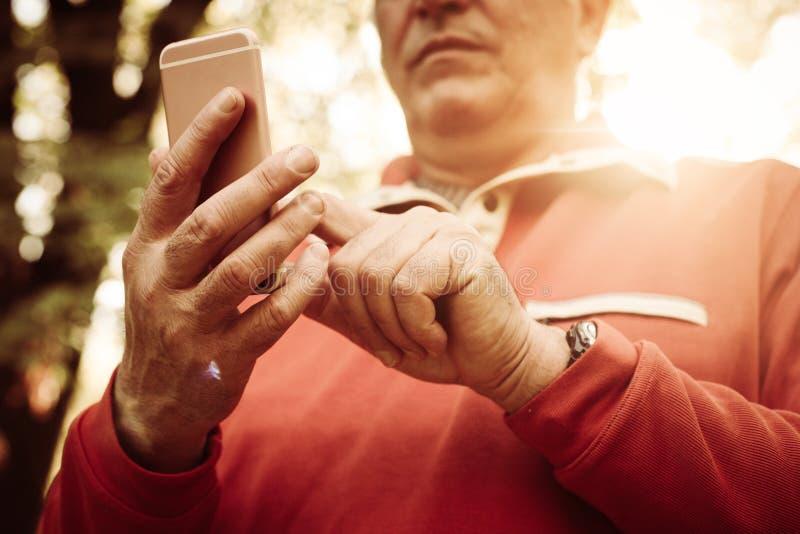 Schließen Sie oben von der älteren Hand im Park unter Verwendung des Handys stockfoto