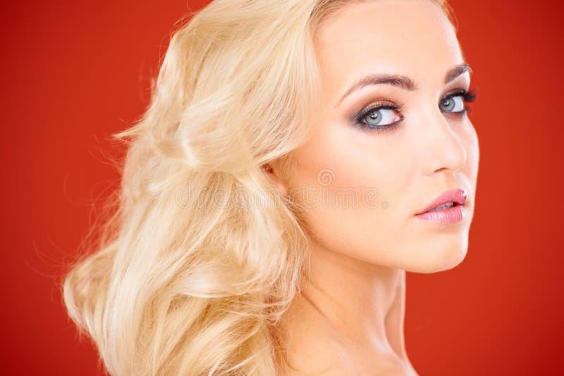 Schließen Sie oben von der blonden Frau gegen roten Hintergrund lizenzfreies stockbild