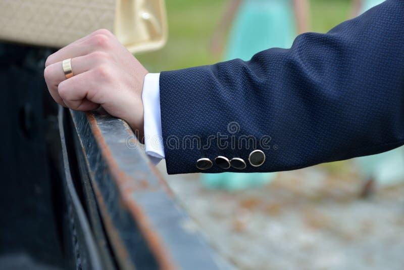 Schließen Sie oben von der eleganten Bräutigamhand mit Ring Er hält die Hand auf t lizenzfreies stockbild