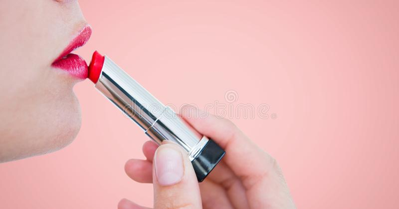 Schließen Sie oben von der Frau, die auf Lippenstift gegen rosa Hintergrund sich setzt lizenzfreies stockfoto