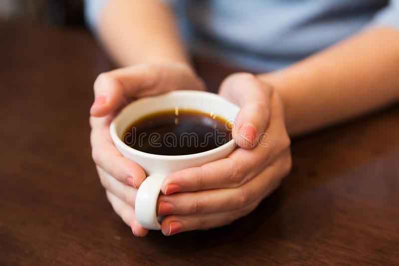 Schließen Sie oben von der Frau, die heiße schwarze Kaffeetasse hält lizenzfreies stockbild