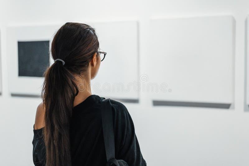 Schließen Sie oben von der Frau, die leere Segeltuchplakate auf der Wand in der Kunstgalerie betrachtet lizenzfreie stockbilder