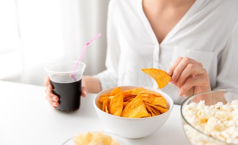 Schließen Sie oben von der Frau, die Mais Nachos mit Kolabaum isst lizenzfreies stockfoto