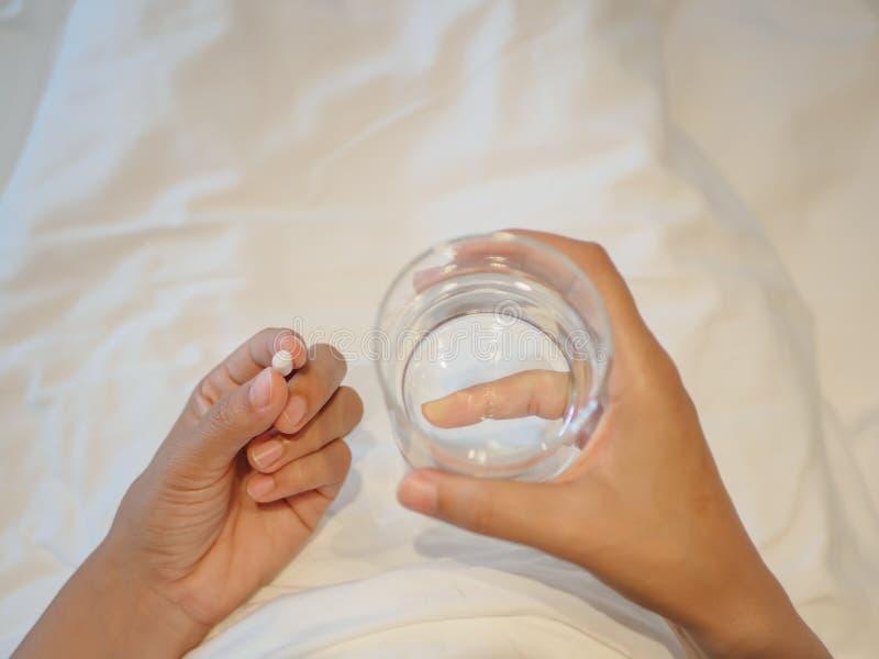 Schließen Sie oben von der Frau, die Pillen mit selektivem Fokus einläßt stockbilder