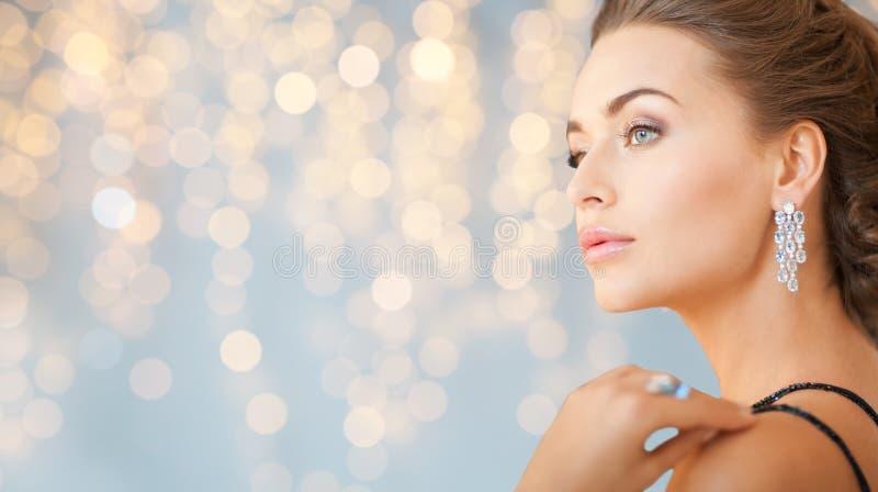 Schließen Sie oben von der Frau mit Diamantohrring lizenzfreie stockbilder