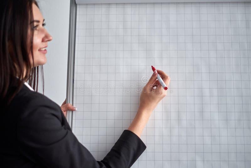 Schließen Sie oben von der Frau mit Markierungsschreiben oder -zeichnung etwas auf Flip-Chart stockfotos
