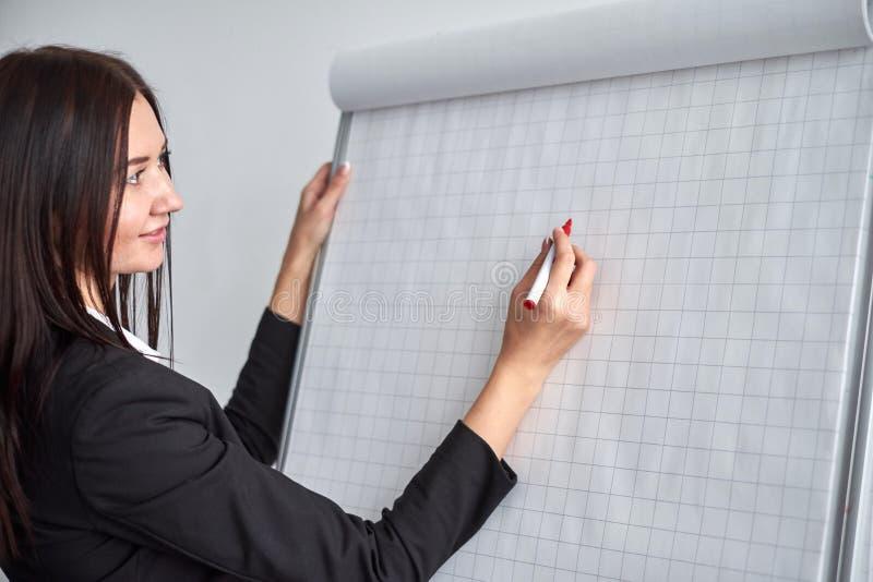 Schließen Sie oben von der Frau mit Markierungsschreiben oder -zeichnung etwas auf Flip-Chart lizenzfreies stockfoto