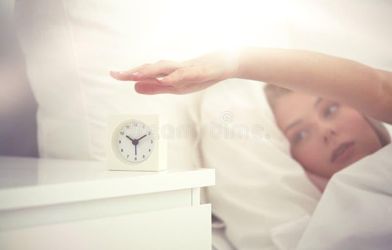 Schließen Sie oben von der Frau mit Wecker im Bett zu Hause stockfotos