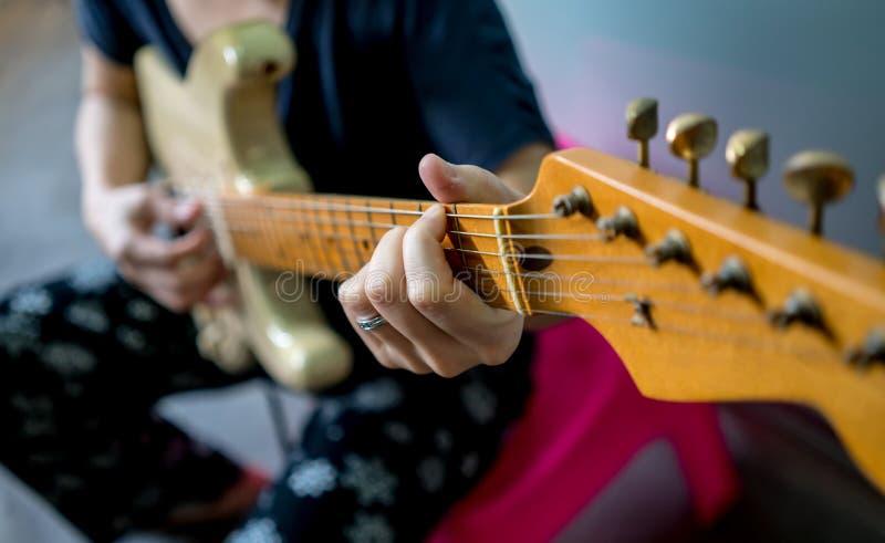 Schließen Sie oben von der Frauenhand, die E-Gitarre spielt stockfotos