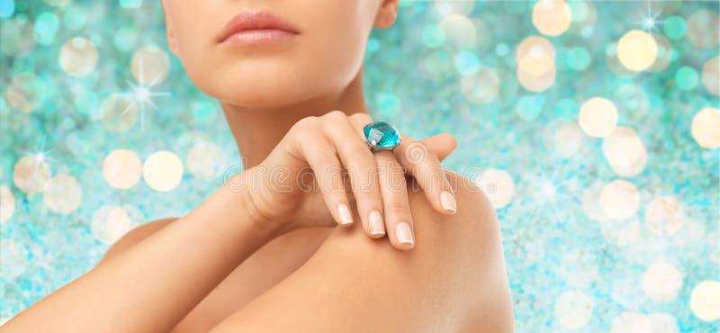 Schließen Sie oben von der Frauenhand mit Ring und kostbarem Edelstein lizenzfreies stockbild
