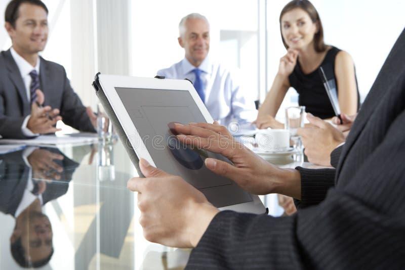 Schließen Sie oben von der Geschäftsfrau Using Tablet Computer während des Brettes Mee stockbild