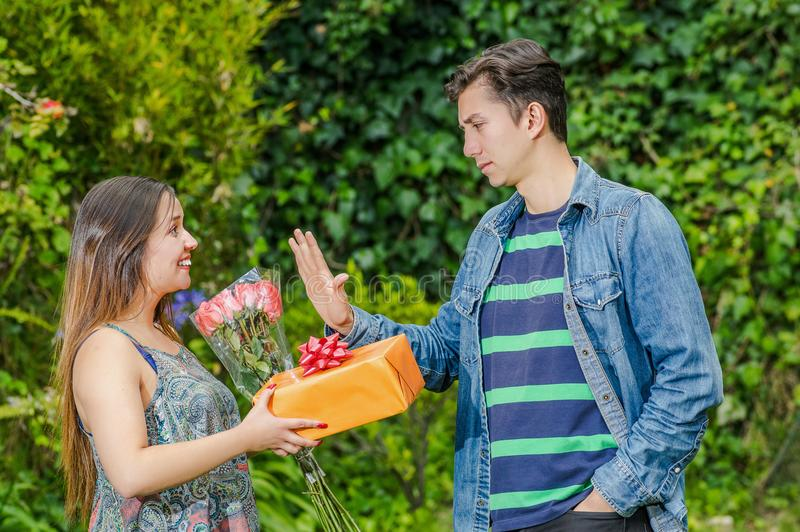 Schließen Sie oben von der glücklichen Frau, die ein Geschenk und Blumen seine Zerstampfung betrachtend halten und vom Jungen, de lizenzfreie stockfotografie