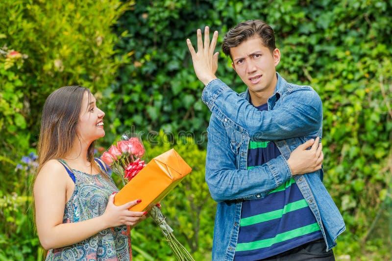 Schließen Sie oben von der glücklichen Frau, die ein Geschenk und Blumen seine Zerstampfung betrachtend halten und vom Jungen, de stockfotos
