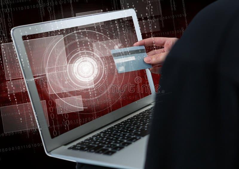 Schließen Sie oben von der Hand des Hackers unter Verwendung eines Laptops beim Halten einer Kreditkarte lizenzfreie abbildung