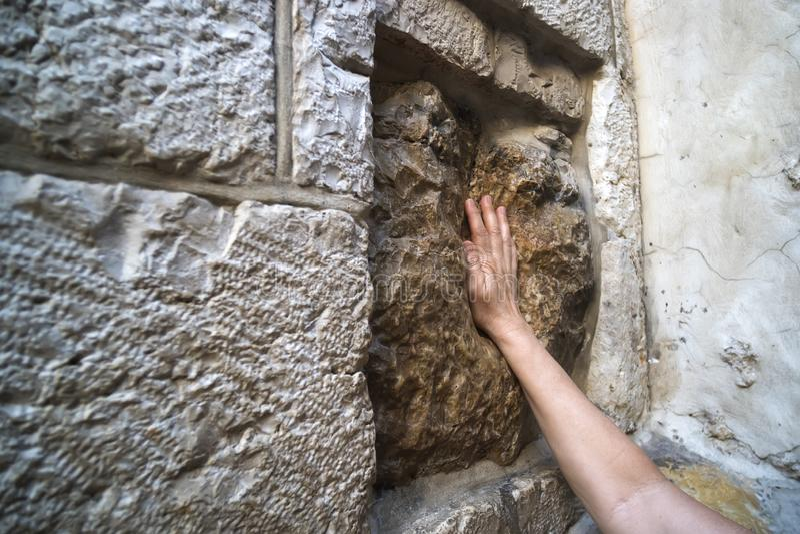 Schließen Sie oben von der Hand des jungen Mannes, die einen alten quadratischen Stein mit einem Hohlraum berührt, der das Impres stockbild