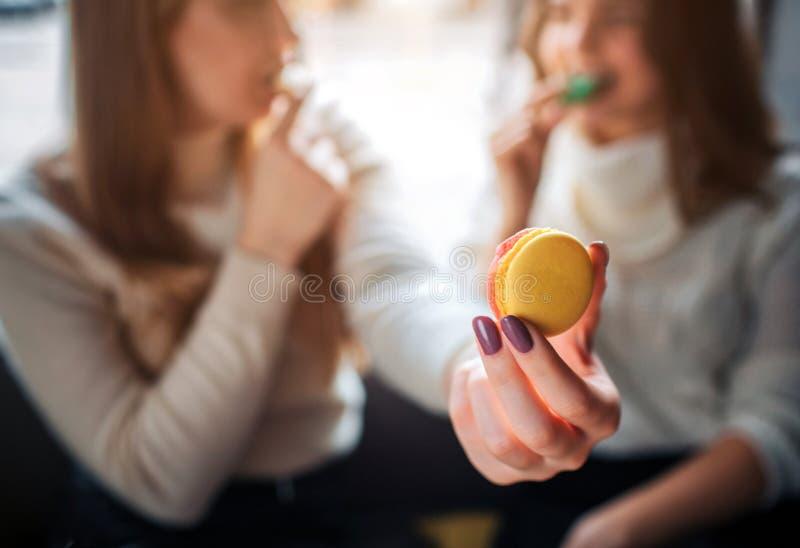Schließen Sie oben von der Hand, die in der Hand gelbes macaron hält Youn g-Frauen essen cookis und betrachten einander Sie sitze stockbilder