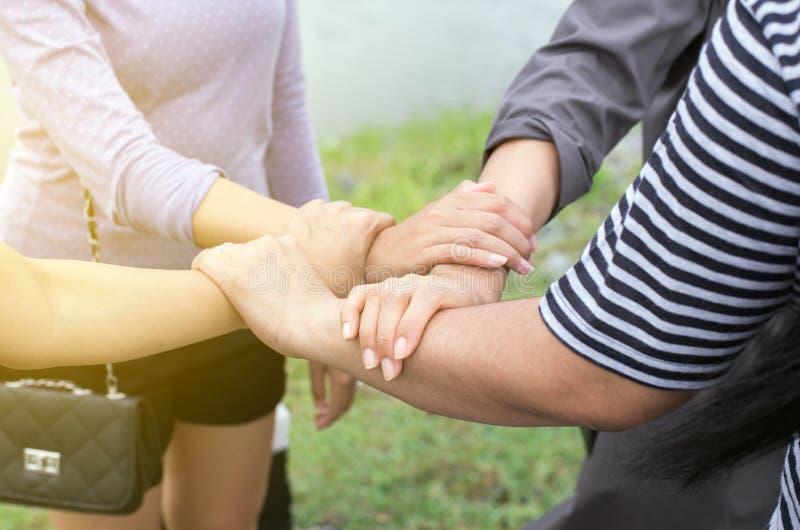 Schließen Sie oben von der Handfrau, die mit Stapel oder Händeschütteln sich setzt und zusammen die erfolgreiche Teamwork im Frei stockfotografie