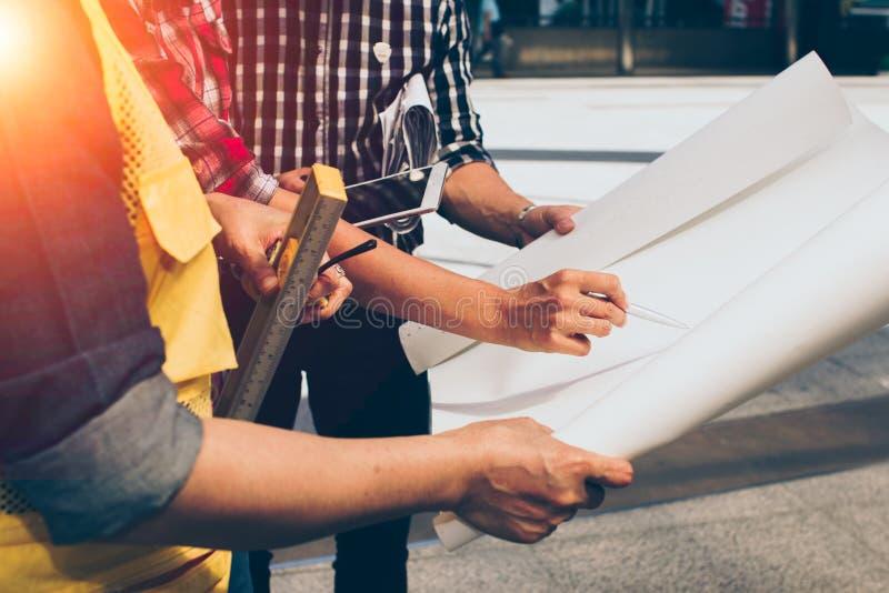 Schließen Sie oben von der Handingenieursitzung für Architekturprojektfunktion mit Partner- und Technikwerkzeugen auf Arbeitsplat lizenzfreie stockfotos