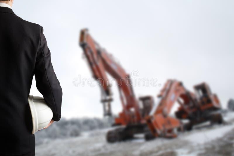 Schließen Sie oben von der Ingenieurhand, die weißen Schutzhelm für die Arbeitskraftsicherheit hält, die vor unscharfer Baustelle stockfotos