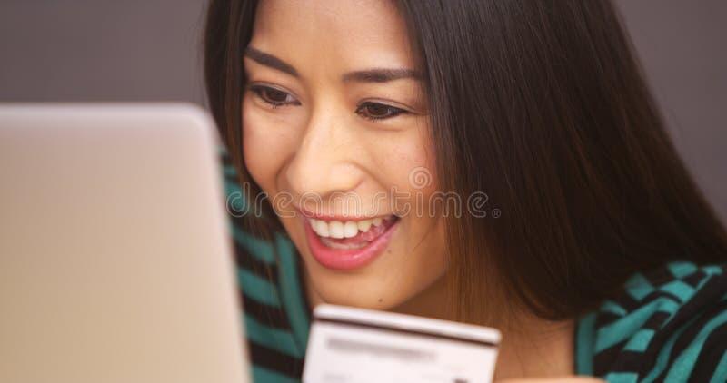Schließen Sie oben von der japanischen Frau, die mit Kreditkarte lächelt stockbilder