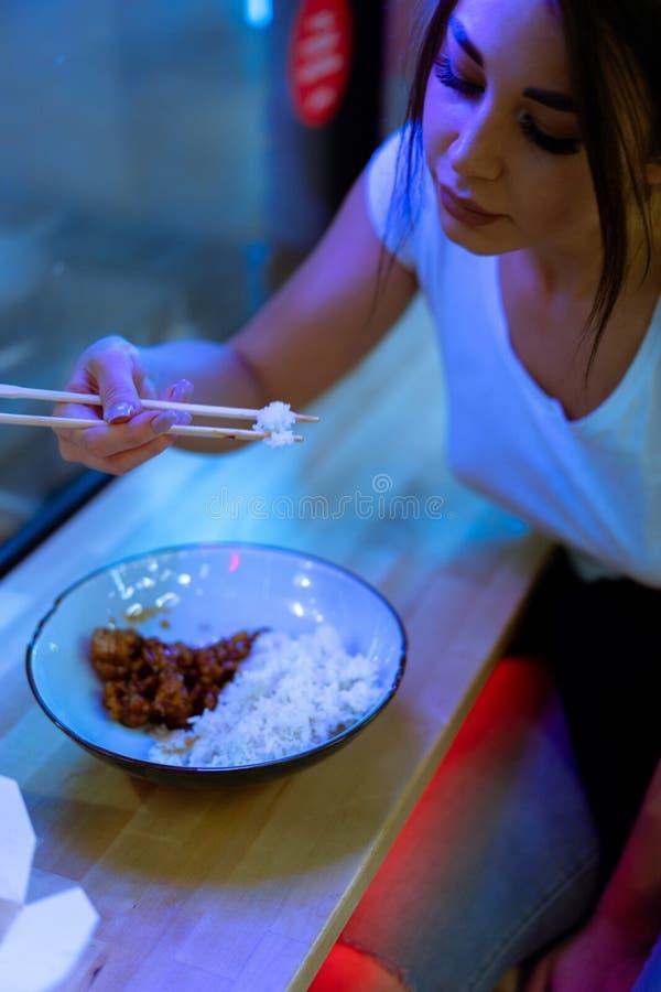 Schließen Sie oben von der jungen attraktiven Frau, die asiatisches Lebensmittel mit Essstäbchen am Café isst lizenzfreie stockfotos