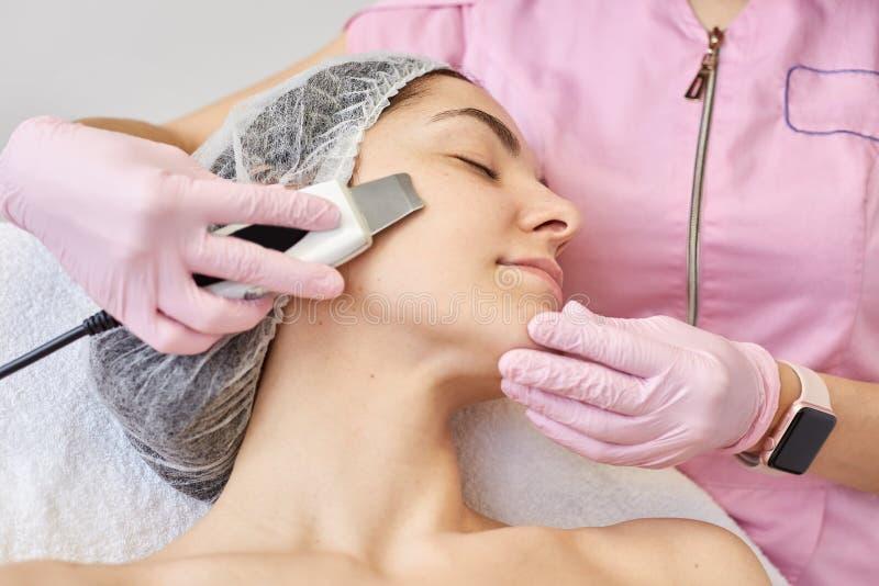 Schließen Sie oben von der jungen attraktiven Frau, die Reinigungsbehandlung der Ultraschallgesichtshaut durch Berufscosmetologis stockbild