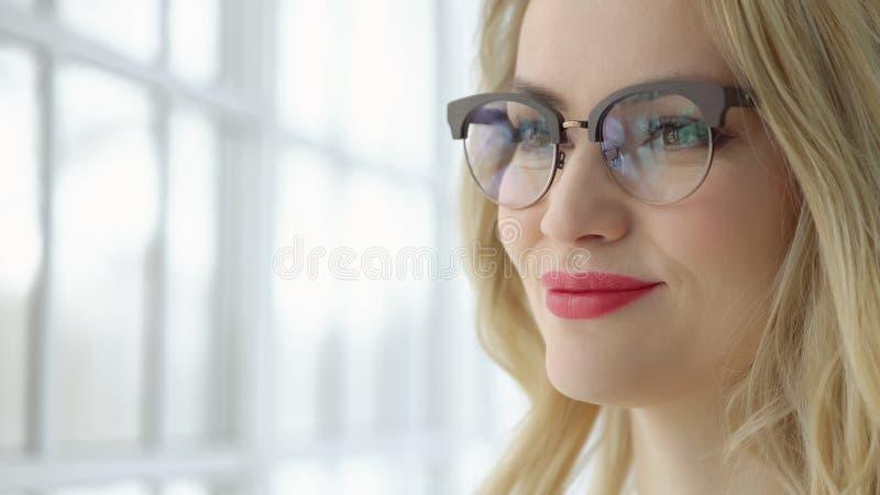 Schließen Sie oben von der jungen Frau in den Gläsern und in einem schwarzen Kleid am Fenster stockbilder