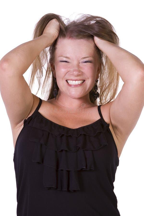 Schließen Sie oben von der jungen Frau, die ihre Haare zieht stockfotos