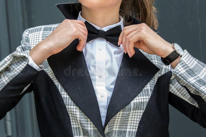 Schließen Sie oben von der jungen Frau, die ihre schwarze Fliege im weißen shi justiert stockbilder