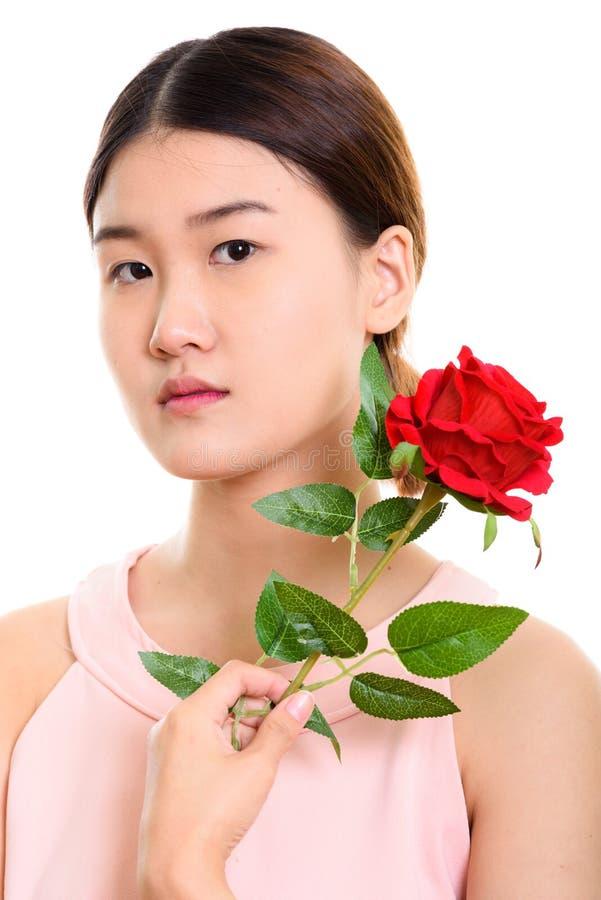 Schließen Sie oben von der jungen schönen Asiatin, die rote Rose nahe Th hält stockbilder