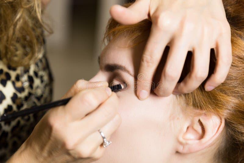 Schließen Sie oben von der jungen schönen Braut, die Make-up durch Make-upkünstler anwendet lizenzfreies stockbild