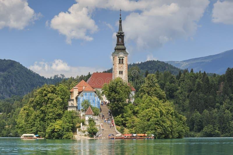 Schließen Sie oben von der Kirche in der Mitte von Bled See mit einigen Touristen, die vorbei gehen stockbild
