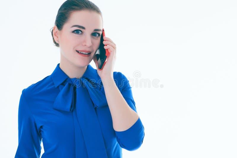 Schließen Sie oben von der lächelnden jungen Frau, die am Handy spricht, der mit der Seite, über weißem Hintergrund schaut lizenzfreies stockfoto