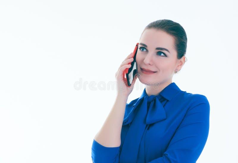 Schließen Sie oben von der lächelnden jungen Frau, die am Handy spricht, der mit der Seite, über weißem Hintergrund schaut stockfotografie