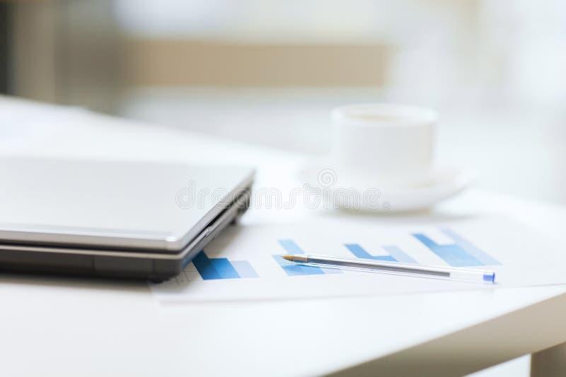 Schließen Sie oben von der Laptop-Computer, den Diagrammen und dem Kaffee lizenzfreie stockfotografie