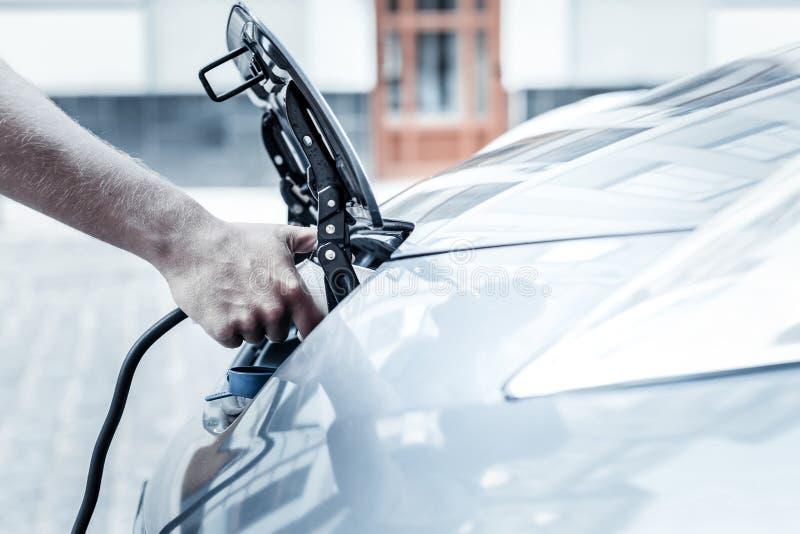Schließen Sie oben von der männlichen Hand, die Aufladungsdüse des Elektroautos hält stockbild