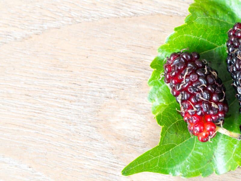 Schließen Sie oben von der Maulbeere mit Blättern eines Grüns auf dem Holztisch Maulbeere dieses eine Frucht und kann herein gege lizenzfreie stockfotografie