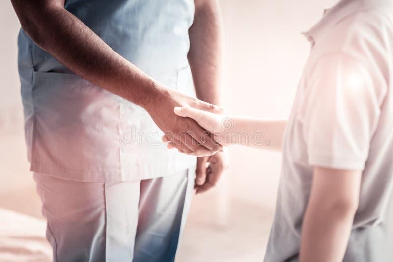 Schließen Sie oben von der medizinischen Arbeitskraft und vom Kind, die Hände rüttelt stockfotos