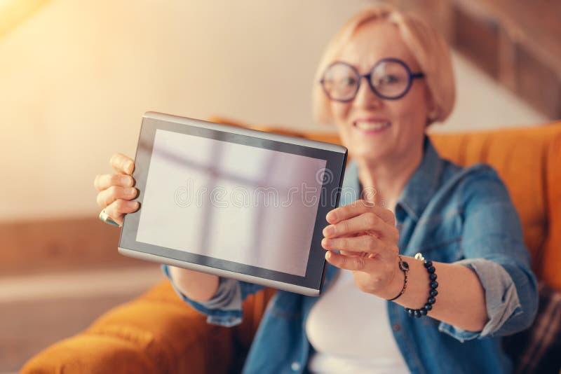 Schließen Sie oben von der modernen Tablette in den Händen der netten Greisin lizenzfreies stockfoto