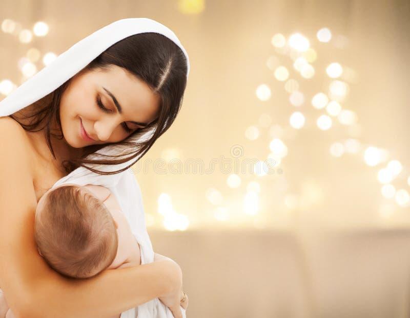 Schließen Sie oben von der Mutter mit Baby über Weihnachtslichtern stockfoto