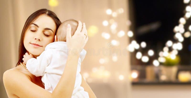 Schließen Sie oben von der Mutter mit Baby über Weihnachtslichtern stockfotos