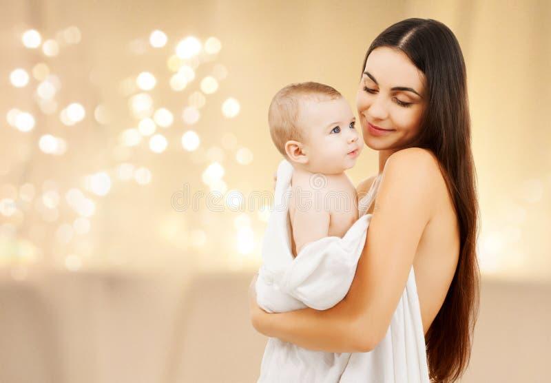 Schließen Sie oben von der Mutter mit Baby über Weihnachtslichtern stockfotografie