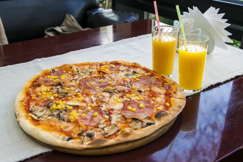 Schließen Sie oben von der Pizza mit Fleisch und Mais und zwei Gläser von orange J lizenzfreies stockfoto