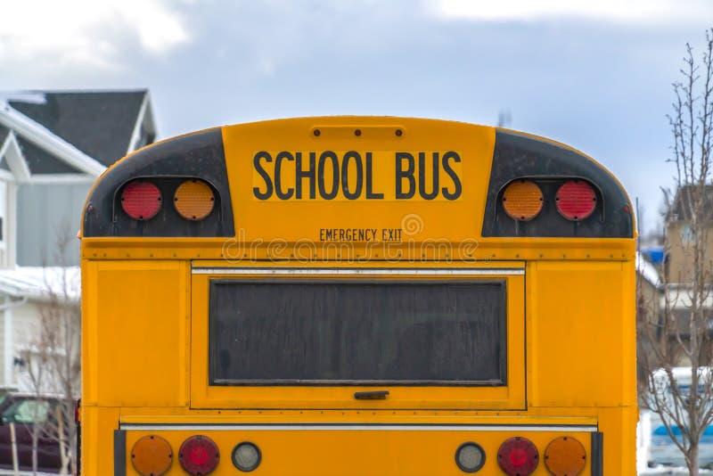 Schließen Sie oben von der Rückseite eines Schulbusses mit einem Fenster und einigen Signallichtern lizenzfreies stockbild