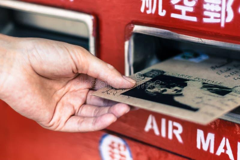 Schließen Sie oben von der weiblichen Hand, die Umschlag in Briefkasten setzt lizenzfreie stockfotografie