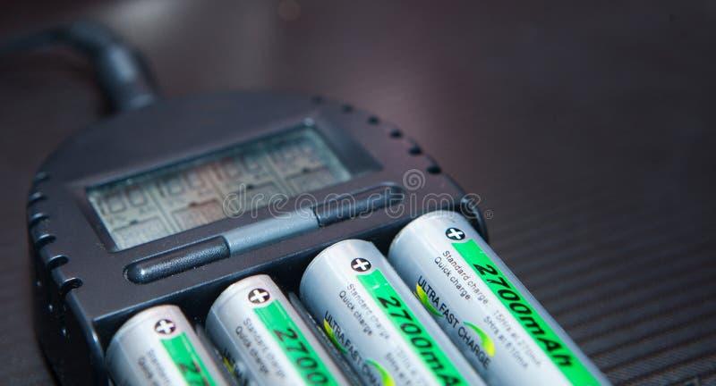 Schließen Sie oben von der wieder aufladbaren Lithium-Ionen-Batterie mit Ladegerät stockfotos