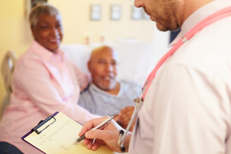 Schließen Sie oben von Doktor Updating Patient Notes stockbild