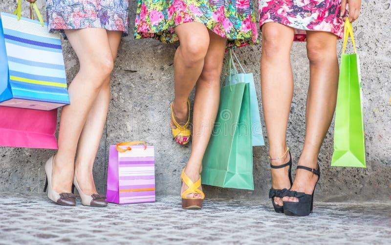 Schließen Sie oben von drei Frauen mit Einkaufstaschen, von der Bodenansicht mit hohen Absätzen und von den Einkaufstaschen lizenzfreie stockbilder