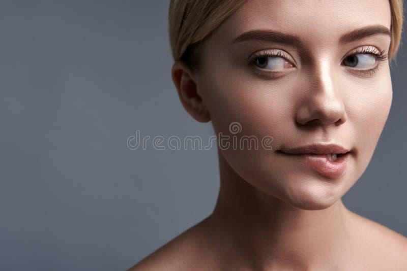 Schließen Sie oben von durchdachter Dame, die ihre Lippe beißt und rechts schaut lizenzfreies stockbild