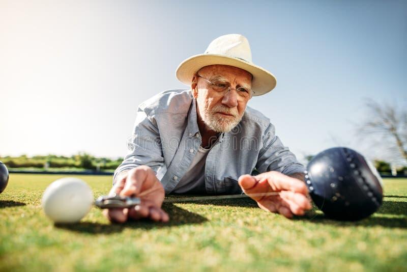 Schließen Sie oben von einem alten Mann, der den Abstand zwischen den Boules misst lizenzfreie stockfotografie